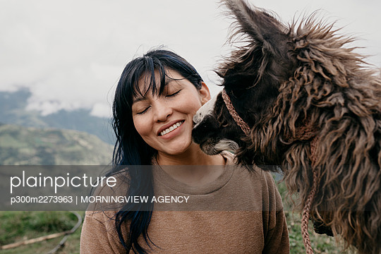 Smiling woman with eyes closed standing by Alpaca - p300m2273963 by MORNINGVIEW AGENCY
