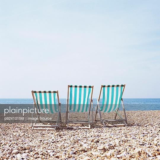 Three deckchairs on a shingle beach - p92410156f by Image Source