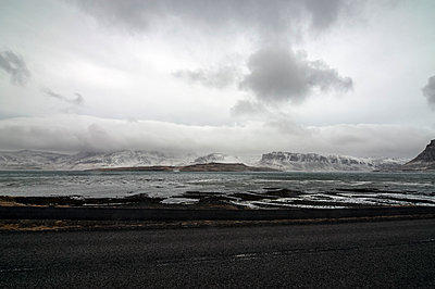 Tarmac road next to bay in Iceland - p1047m1531871 by Sally Mundy