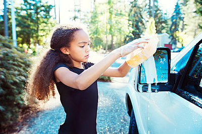 Girl washing car while standing at driveway - p1166m1225973 by Cavan Images