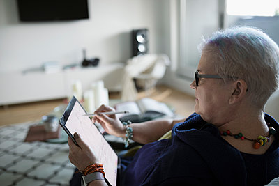 Senior woman drawing with stylus and digital tablet in living room - p1192m1517054 by Hero Images