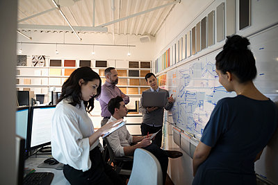 Designers brainstorming, meeting at whiteboard in creative office - p1192m1529976 by Hero Images