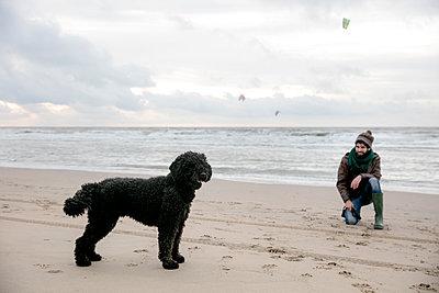 Mann und Hund am Strand - p1212m1185500 von harry + lidy