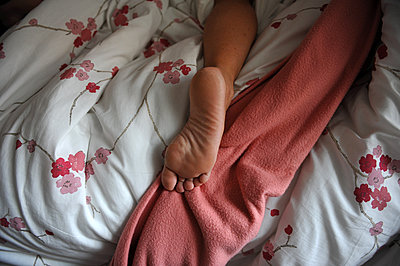 Person lying barefoot on bed - p1468m1539356 by Philippe Leroux