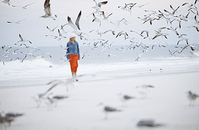 Woman walking next to the ocean surrounded by flying seagulls - p1577m2150315 by zhenikeyev