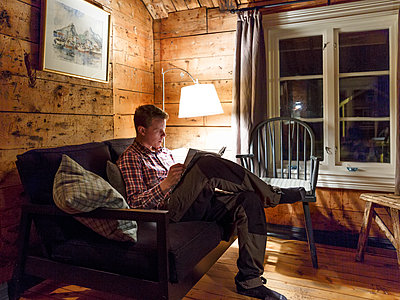 Young man reading book at night - p312m1063523f by Stefan Isaksson