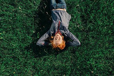 Caucasian teenage girl laying in grass - p555m1531620 by Vladimir Serov