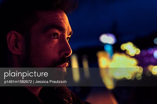 Hipster Mann schaut im bunt beleuchteten Park in die Ferne - p1491m1582672 von Jessica Prautzsch