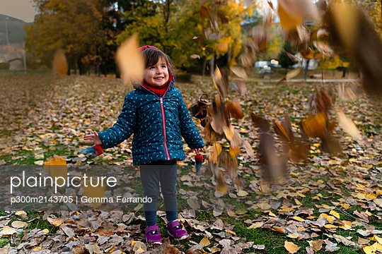 Little girl playing with autumn leaves outdoors - p300m2143705 by Gemma Ferrando
