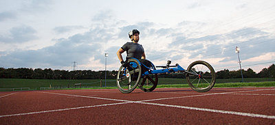 Determined young female paraplegic athlete training for wheelchair race on sports track - p1023m2067532 by Martin Barraud