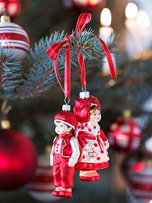 Little boy and girl Christmas tree baubles hung from branch with red ribbon - p1183m997814 by Manduzio, Matteo