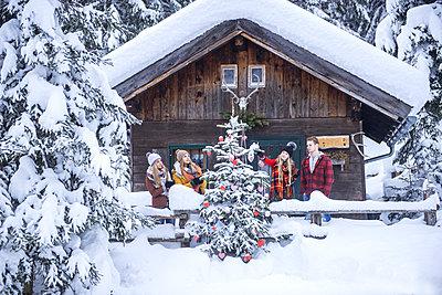 Austria, Altenmarkt-Zauchensee, friends decorating Christmas tree at wooden house - p300m1505624 by Hans Huber