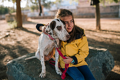 Cute girl hugging dog while sitting on rock - p300m2198771 by LUPE RODRIGUEZ