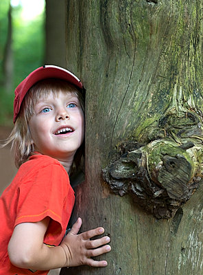 Austria, Boy leaning on tree trunk, smiling - p300m2207196 by Monk68