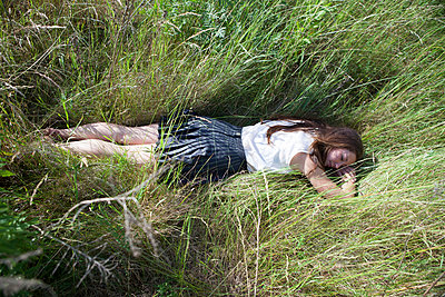 Young woman lying on a meadow - p502m924236 by Tomas Adel