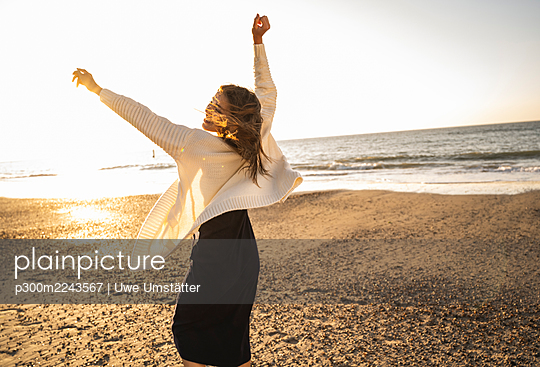 Carefree woman dancing at beach against sky during sunny day - p300m2243567 by Uwe Umstätter