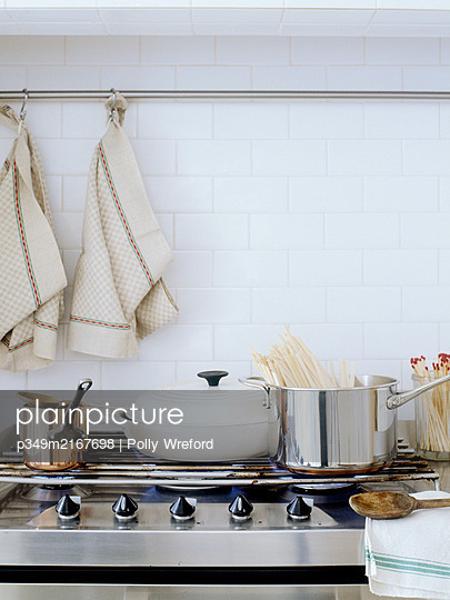 Assorted pans on gas hob with dishcloths. - p349m2167698 by Polly Wreford