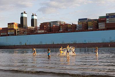 Kinder am Elbstrand mit Containerschiff - p076m2014663 von Tim Hoppe