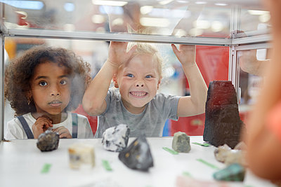 Silly girl making a face at rock exhibit display case in science center - p1023m2016983 by Trevor Adeline