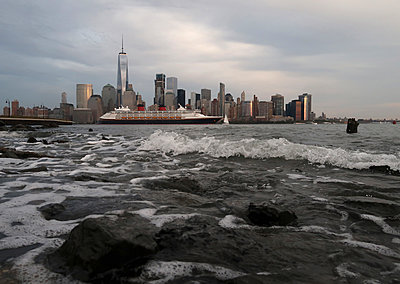 Cruise ship in river against cityscape in New York city - p1166m1209486 by Cavan Images