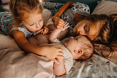 Two girls touching baby sibling and cuddling in bed together - p1166m2212391 by Cavan Images