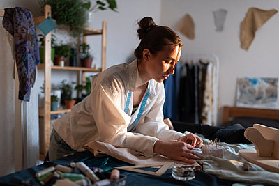 Young designer working with fabrics at home - p1166m2218574 by Cavan Images