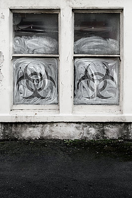 Biohazard symbols on whitewashed window - p1280m2182459 by Dave Wall