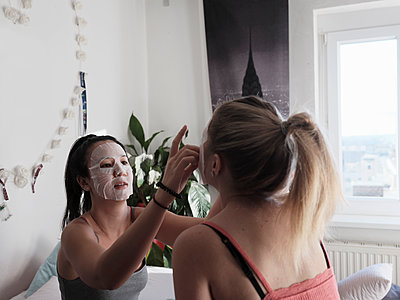Zwei Freundinnen tragen Gesichtsmasken - p1383m2045106 von Wolfgang Steiner