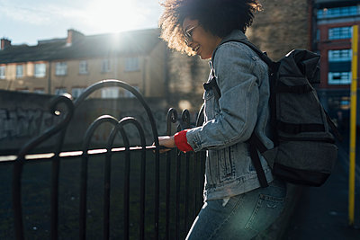 Carefree young woman with backpack standing by railing in city on sunny day - p300m2213914 by Boy photography