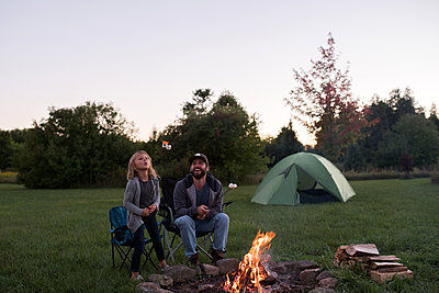 Father and daughter sitting beside campfire, toasting marshmallows over fire - p924m1197087 by Kymberlie Dozois Photography
