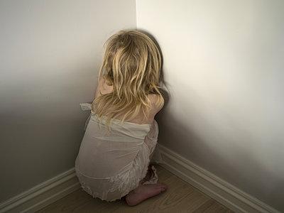 Kleines Mädchen kauert in einer Ecke - p945m1161585 von aurelia frey