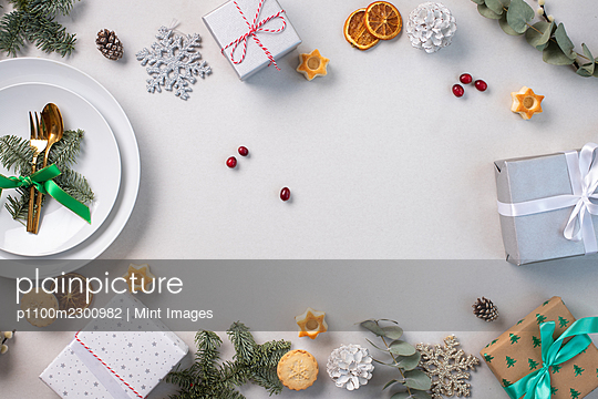 Christmas decorations on a white background, green leaves and red berries - p1100m2300982 by Mint Images