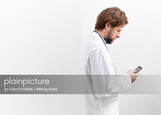 Junger Arzt mit Smartphone - p1124m1216826 von Willing-Holtz