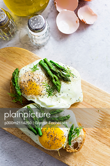 Slices of baguette garnished with fried eggs and Asparagus on a plate - p300m2114250 von Giorgio Fochesato