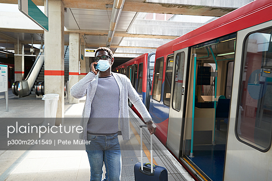 Mature businessman wearing protective face mask talking on phone at railroad station platform - p300m2241549 by Pete Muller
