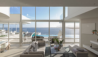 Sunny, tranquil modern luxury home showcase interior living room with patio and ocean view - p1023m1406961 by Martin Barraud