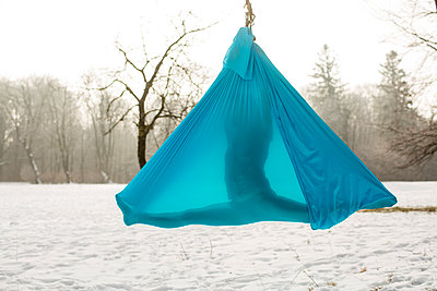 Young woman practicing aerial yoga outdoors - p1026m1025129f by Patrick Frost