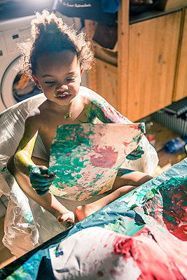 Girl draws red picture with fingercolors and is fully smeared of colors - p300m1157131 by YesyesNono Fotografie
