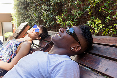 Relaxed happy couple lying on sun loungers wearing sunglasses - p300m1563138 by Authentic Images