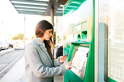 Spain, Barcelona, woman buying ticket from automated machine at  station - p300m1588206 by Valentina Barreto