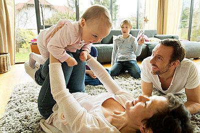 Familie im Wohnzimmer spielt zusammen - p341m1137186 von Mikesch
