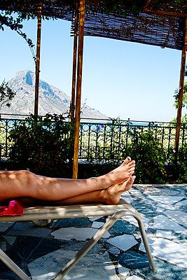 Greece, Kalymnos, Woman´s legs on sun lounger - p352m1186952 by Lena Katarina Johansson