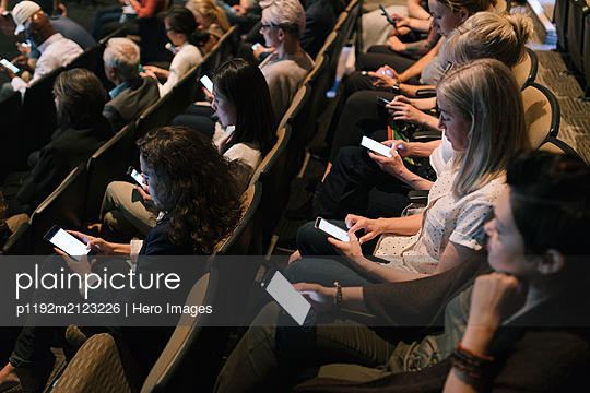 Audience using smart phones during presentation - p1192m2123226 by Hero Images