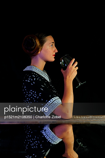 Young woman in retro dress holding a glass of wine - p1521m2108350 by Charlotte Zobel