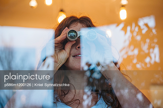 Junge Frau blickt durch ein Fernglas - p586m1200126 von Kniel Synnatzschke