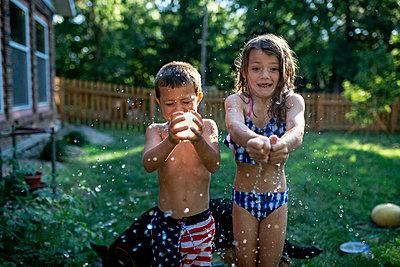 Playful siblings bursting water bombs while standing at backyard - p1166m2025411 by Cavan Images