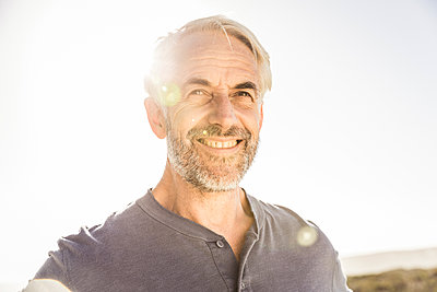 Portrait of smiling grey-haired man at sunset - p300m2167017 by Floco Images