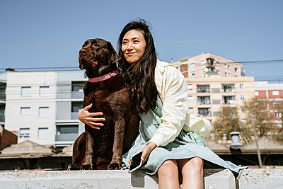 Smiling woman sitting with Chocolate Labrador on retaining wall in front of building - p300m2273520 by VITTA GALLERY