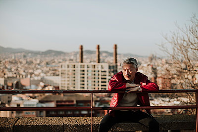 Mature man wearing jacket sitting on retaining wall while city in background - p300m2274773 by Gala Martínez López