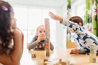 Boy stacking alphabet blocks on table - p426m1131075f by Maskot